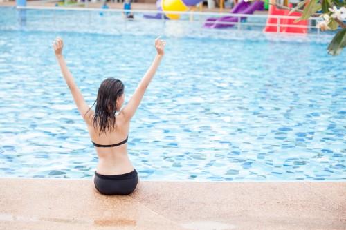 プールサイドで腰を下ろし両手を掲げる女性