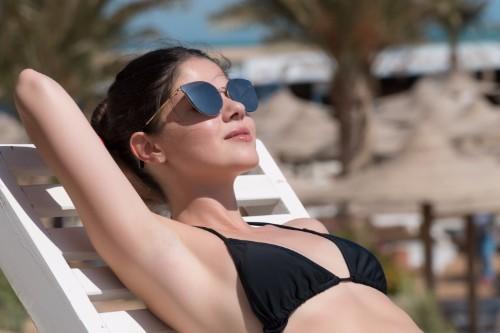日光浴をするサングラスをかけた女性