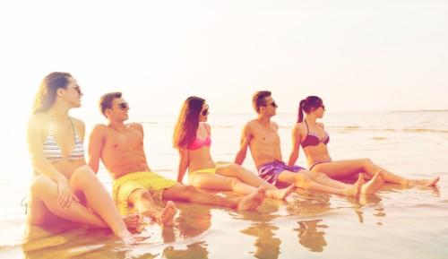 波打ち際で黄昏るおしゃれな五人の男女