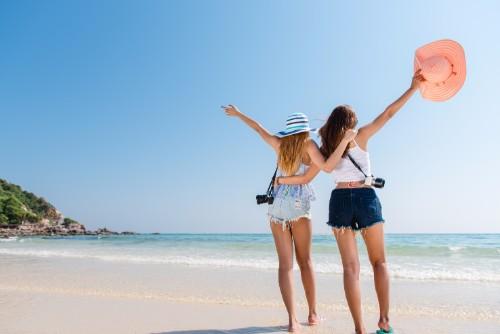 旅行先の綺麗な海を見て喜ぶ二人の女性