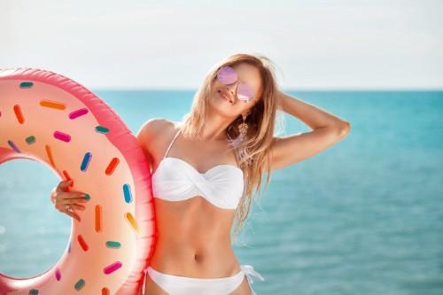 笑顔で浮輪を抱える水着女性