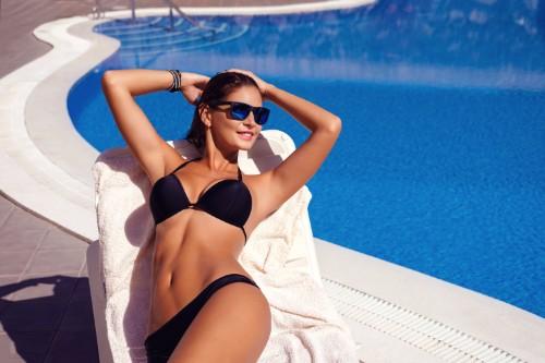 プールサイドでくつろぐ水着女性