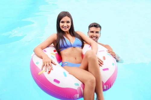 彼氏と楽しそうにプールで遊ぶ水着の女性